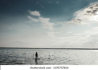 A boy standing in the lake in the morning. The child gets into the water in the dark. Creative background, mysticism, the concept of loneliness, forgetfulness.