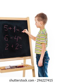 Boy standing nearby board and answering some math exercise