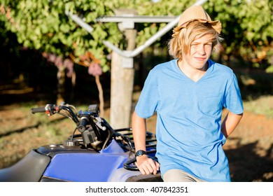 Boy standing next to truck in vineyard