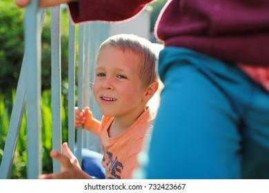 The boy is standing on the bridge