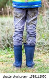 Boy standing on the green wearing blue wellies.