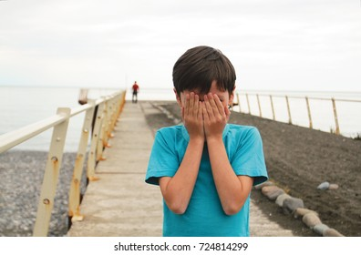 Boy standing on the pier against the sea hid his face with hands.