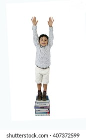 Boy standing on a stack of books isolated on white background