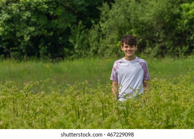 boy standing in a patch of ferns on a country walk