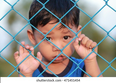 The boy standing of  pulling a metal fence .