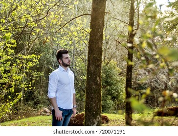 Boy standing sideways in the forest. Boy standing on his side, watching in the woods.