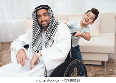 The boy stands behind the Arab man in a wheelchair. The man is disabled and he is at home. On his head wearing keffiyeh.