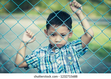 The boy stands behind the fence with emotional expression.