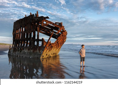 Boy stands by the Peter Iredale shipwreck in the golden sunset light in northwest Oregon.