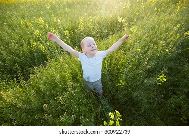 boy stands in a clearing arms outstretched to the sides
