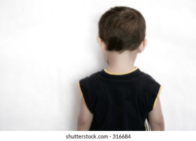Boy stands facing the wall