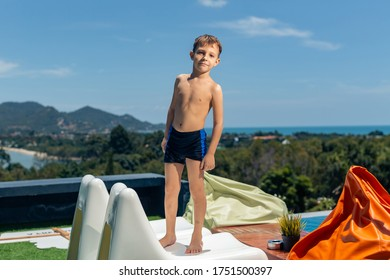 boy stands in front of the pool