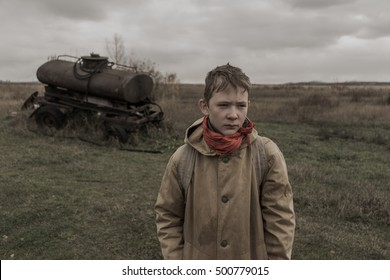 boy stands near an abandoned tank. boy standing in a field. wandering boy. Post apocalypse. Boy traveling on foot in a post-apocalyptic world in search of food. post-apocalyptic world.