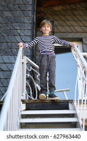 The boy stands on the landing of a metal staircase, holding on to the handrails