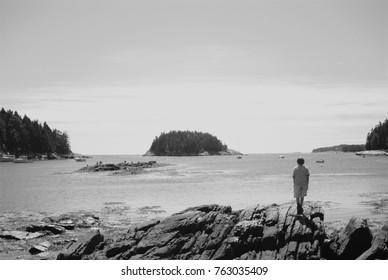 A boy stands on the rocky shore, looking out at islands and the ocean. Photographed in Georgetown, ME in September 2010.