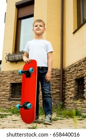 Boy stands with skateboard