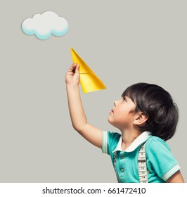 A boy starts a paper airplane in the sky with painted clouds.