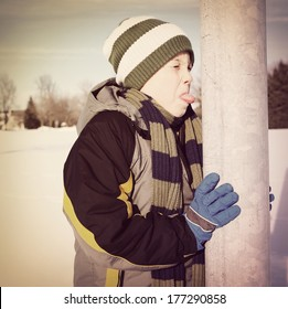 Boy sticking his tongue on a metal pole