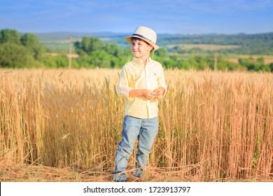 A boy in a straw hat stands near a yellow wheat field, looks away, smiles.