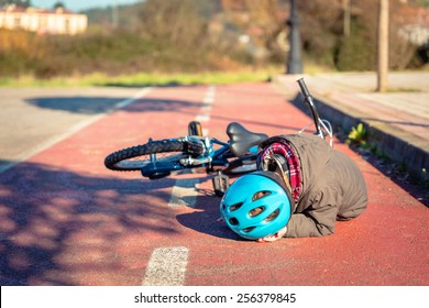 Boy in the street ground touching his head protected with a helmet after falling off to his bicycle