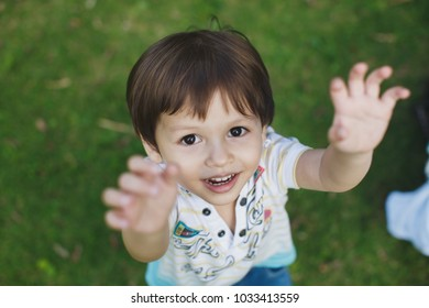 boy stretches his hands to his father