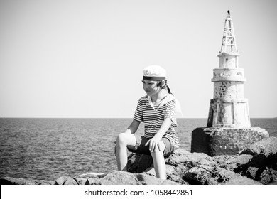 A boy in a striped T-shirt and cap sits on the rocks. In the background stands a lighthouse. Black and white. Stylization, vignetting.