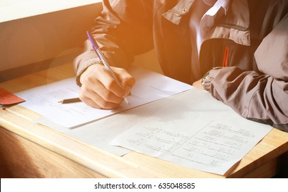 boy student testing in exercise paper, exams answer sheets on wood table in classroom