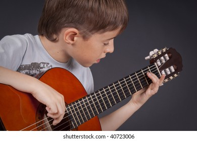 The boy studies to play on a guitar on a black background