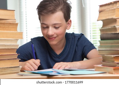 Boy studing at table on blue background and many book