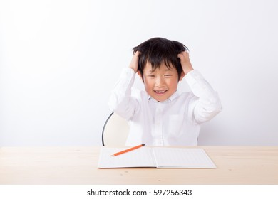 boy studying or doing homework and having difficulty