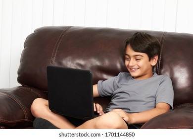boy studying with a laptop sitting on the sofa at home
