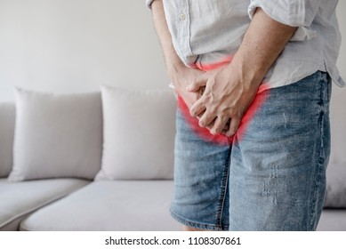 Boy is suffering and holding his genitals on white background with copy space. Man Covering His Crotch. Male suffering with pain in the urogenital system. Disease for men.