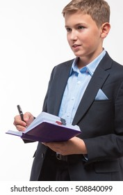Boy in a suit with a diary and a pen in hand on white background