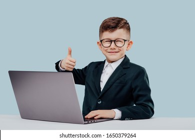 boy in suit and glasses smiling and approving work in office while browsing laptop against blue background
