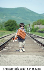 Boy with suitcase and toy on railway station wait a train. Little boy running for a train