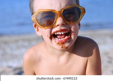 Boy in the sun glasses, soiled by chocolate. Beach./Sweet life