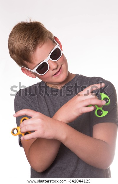 Boy in Sunglasses and Silly Pose with two Fidget Spinners