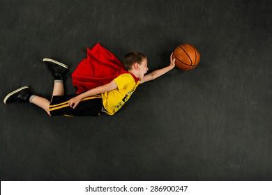 Boy superhero with a basketball
