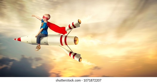 Boy in superhero costume fly on a rocket and show super abilities.