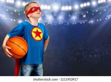 A boy in a superhero costume plays basketball.