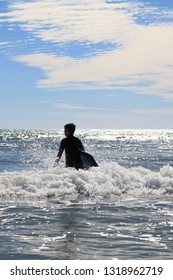 Boy with surf board walking into sea, against a blue slightly cloudy sky