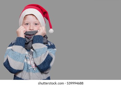 Boy in sweater scarf and hat of Santa Claus on grey background. Isolated on grey. Place for text.
