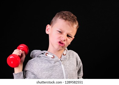 Boy in sweatshirt doing a workout with red dumbbells