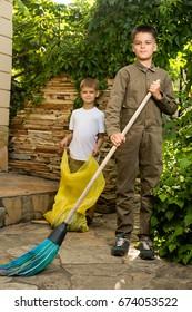 Boy sweeps the yard