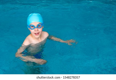 Boy swimmer in swimming pool. Kid with swimming cap and swimming goggles. Child practice water sport. Blue colour swimming pool.