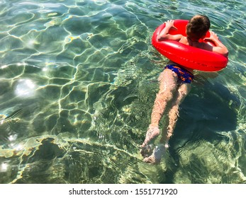 The boy is swimming. Baby swimming in a red rubber lifebuoy. Beach holidays in the Mediterranean Sea, Montenegro, Adritica, Balkans.