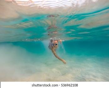 Boy swimming in a clear caribbean sea