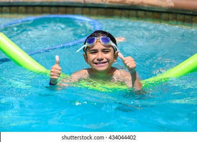 boy swimming with a green foam noodle in a indoor pool