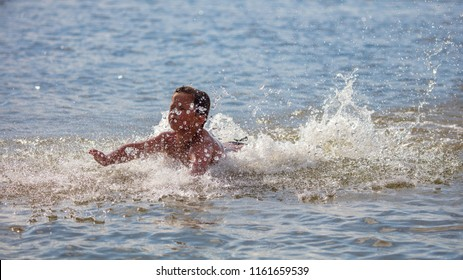 The boy is swimming on the beach