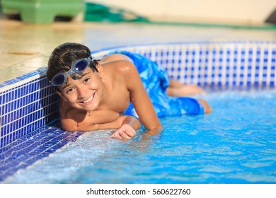 Boy swimming in a pool smiling and having a happy day